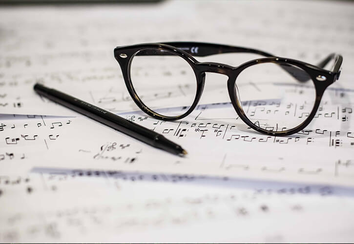 Image of a pair of reading glasses and a pen on top of sheet music. | About Sylvia Moy